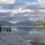 photograph of a pair sitting at the dock of lake mcdonald in Montana