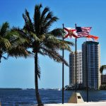 Photograph of a couple of highrise buildings behind US and FLORIDA STATE flags